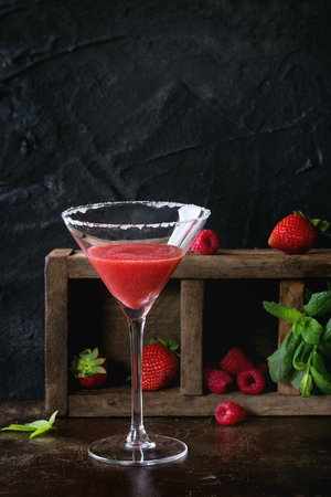 sugared: Sugared glass with strawberry dessert cocktail, served on dark background with Strawberries, raspberries and mint behind. With copy space