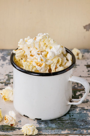 enameled: Prepared salted popcorn served in vintage white enameled mug over old white wooden background. With space for text.