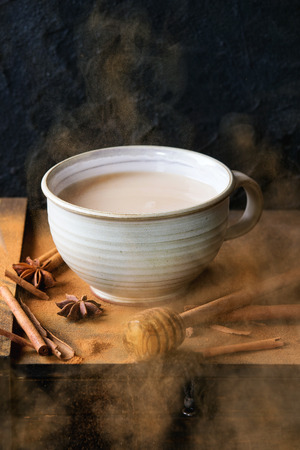 masala chai: White ceramic cup of hot masala chai, served with honey on honey dipper, anise, cinnamon sticks and powder over black wooden box over black textured background. With exploded cinnamone powder Stock Photo