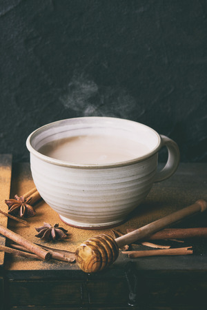 masala chai: White ceramic cup of hot masala chai, served with honey on honey dipper, anise, cinnamon sticks and powder over black wooden box over black textured background. With retro filter effect