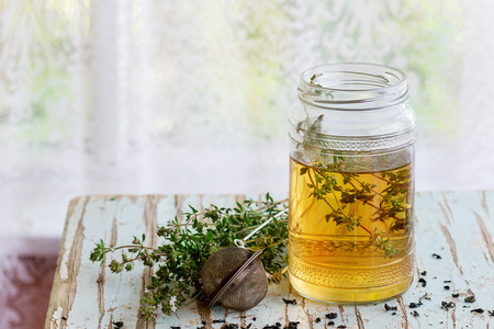 water thyme: Glass jar of hot herbal tea with bunch of fresh thyme, served with vintage tea-strainer on old wooden stool with window at background. Rustic style, natural day light.