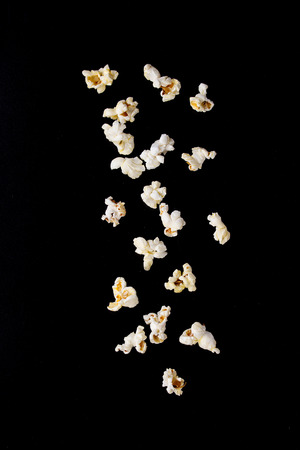 buttered: White prepared salted buttered popcorn isolated over black background. Stock Photo