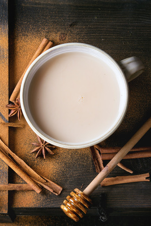 masala chai: White ceramic cup of hot masala chai, served with honey on honey dipper, anise, cinnamon sticks and powder over black wooden textured background. Flat lay