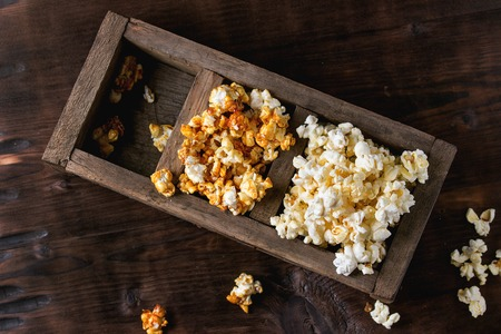 sectioned: Prepared salted and caramelized sweet popcorn in old wood three sectioned box over dark textured wooden background. Top view. With space for text Stock Photo
