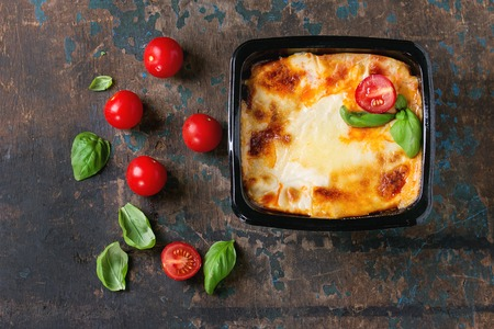 semifinished: Cooked meat lasagna in black plastic box, served with fresh cherry tomatoes and basil leaves over old dark wooden textured background. Market semifinished theme. Space for text