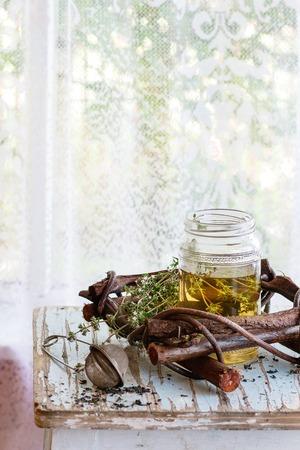 Glazen pot van hete kruidenthee met bos van verse tijm, geserveerd met vintage theezeefje op oude houten kruk met venster op de achtergrond. Rustieke stijl, natuurlijk daglicht.