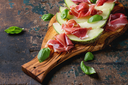 jambon: Sliced melon with ham and basil leaves, served on olive wood chopping board over old wooden textured background.