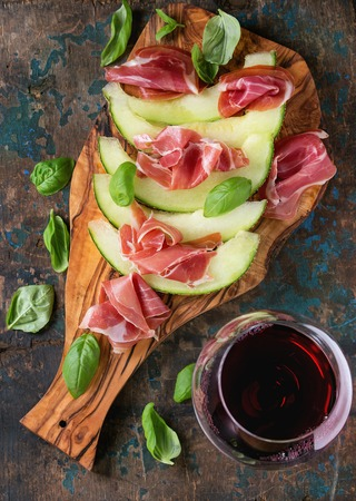 jambon: Sliced melon with ham and basil leaves, served on olive wood chopping board with glass of red wine over old wooden textured background. Top view
