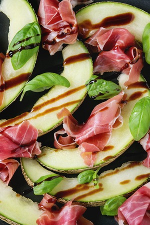 jambon: Food background with sliced melon, ham, basil leaves and balsamic sauceClose up. Top view.