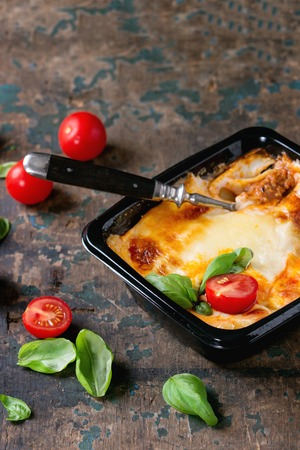 semifinished: Cooked meat lasagna in black plastic box, served with vintage fork,  fresh cherry tomatoes and basil leaves over old dark wooden textured background. Market semifinished theme. Stock Photo
