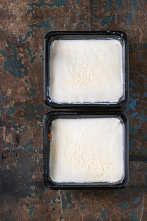 prepack: Two uncooked lasagna in black plastic box over old dark wooden textured background. Market semifinished theme. Top view with copy space