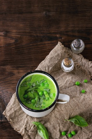 White vintage mug with pea cream soup with sliced basil, served with salt and pepper shakers on sackcloth over dark wooden background. Top view with copy space