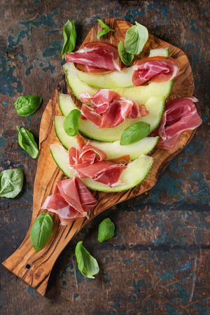 jambon: Sliced melon with ham and basil leaves, served on olive wood chopping board over old wooden textured background. Top view. With space for text
