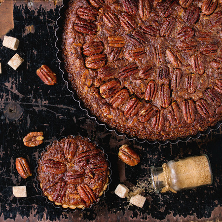 pecan pie: Homemade Big round caramel pecan pie and small tartlets in black iron forms, served with brown sugar over old black wooden background. Flat lay. Square image Foto de archivo