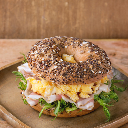 sprinkle seeds Whole Grain bagels with scrambled eggs, pea sprout and prosciutto ham on wood plate over wooden textured background. Square image
