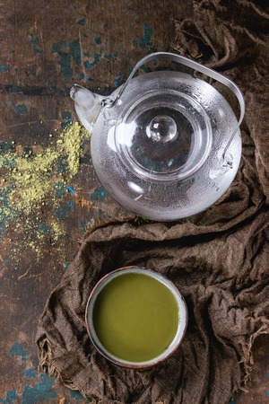 maccha: Ceramic cup of green matcha tea with glass teapot with hot water on wet sackcloth rag over dark wooden textured background. Healthy food. With copy space. Top view Stock Photo
