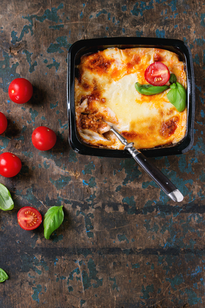 semifinished: Cooked meat lasagna in black plastic box, served with vintage fork,  fresh cherry tomatoes and basil leaves over old dark wooden textured background. Market semifinished theme. Top view