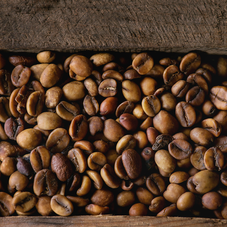 decaf: Food background with Green and brown decaf unroasted and black roasted coffee beans in old wooden box. Top view. Close up. Square image