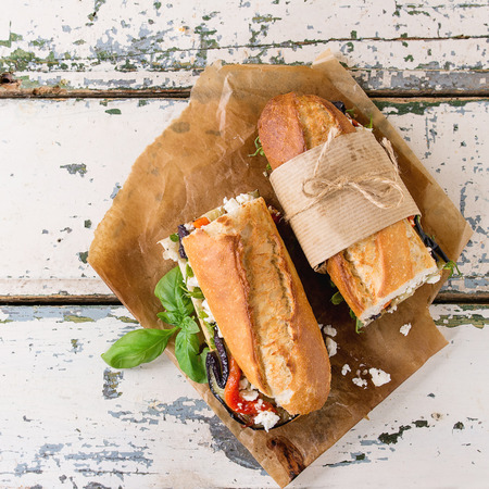 two and a half: Two half of vegetarian baguette submarine sandwich with grilled eggplant, pepper and feta cheese served on baking paper over old white wooden background. Top view. Square image Stock Photo