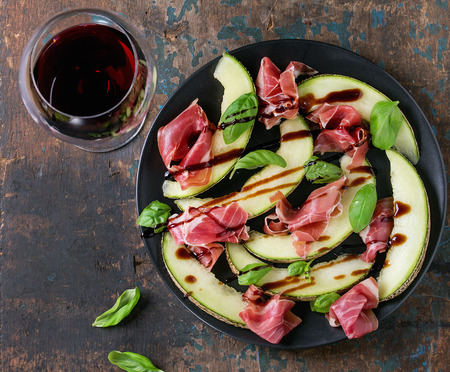 jambon: Sliced melon with ham, basil leaves and balsamic sauce, served on black plate with glass of red wine over old wooden textured background. Top view. With space for text Stock Photo