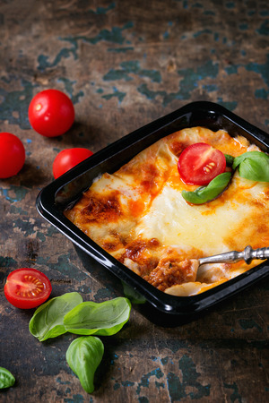 prepack: Cooked meat lasagna in black plastic box, served with vintage fork,  fresh cherry tomatoes and basil leaves over old dark wooden textured background. Market semifinished catering theme.