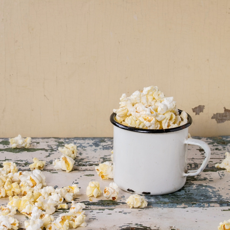 enameled: Prepared salted popcorn served in vintage white enameled mug over old white wooden background. With space for text. Square image
