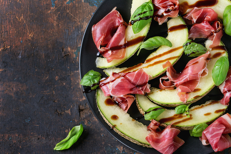 jambon: Sliced melon with ham and basil leaves, served on black ceramic plate over old wooden textured background. Top view. With space for text