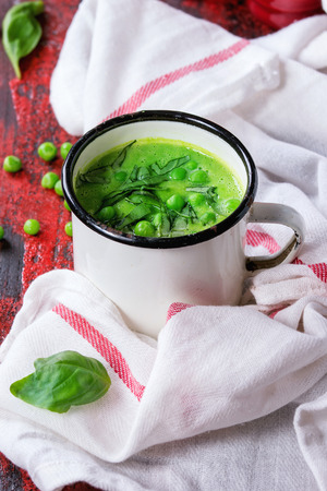 White vintage mug with pea cream soup with sliced basil, served with red salt and pepper shakers on white kitchen towel over red and black wooden background.