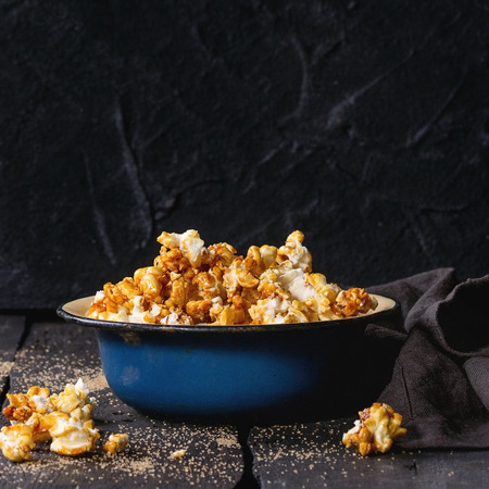 enameled: Caramelized sweet popcorn served in vintage enameled bowl with brown sugar and textile napkin over dark wooden background. Square image Stock Photo