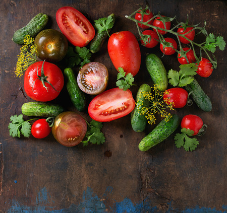 Food background with tomatoes, cucumbers and herbs. Vegetables salad seasonal theme with space for text. Healthy food concept. Top view Stock Photo