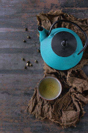 copy sapce: Handmade ceramic cup of hot green tea, served with blue iron teapot on wet sackcloth over old dark textured background. Asian style. Top view with copy sapce Stock Photo