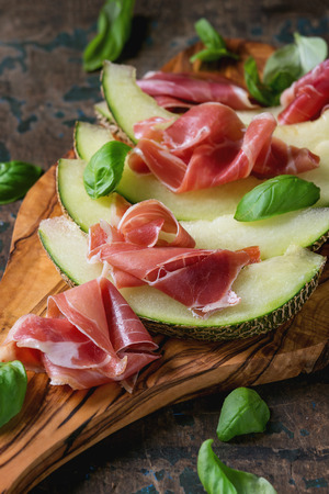 Sliced melon with ham and basil leaves, served on olive wood chopping board over old wooden textured background.