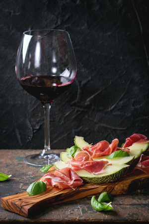 jambon: Sliced melon with ham and basil leaves, served on olive wood chopping board with glass of red wine over old wooden textured background. With space for text Stock Photo
