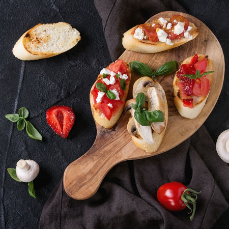 Various of mini bruschetta with tomatoes, strawberries, feta cheese, chicken, mushrooms and basil on toasted baguette, served on olive wood chopping board over black background. Flat lay, square image Stock Photo