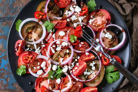 plato de ensalada: Black plate with sliced different tomatoes, red onion, balsamic sause, parsley and feta cheese salad, served with fork on wet sackcloth rag over old dark wood textured background. Top view Foto de archivo