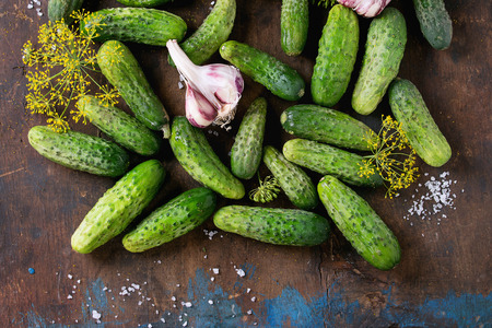 pickling: Food background. Cucumbers with garlic, salt and dill for pickling over old wooden surface. Top view Stock Photo