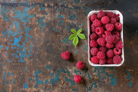 hojas antiguas: Paper market box of fresh raspberries with leaves over old wooden textured background. Top view with copy space