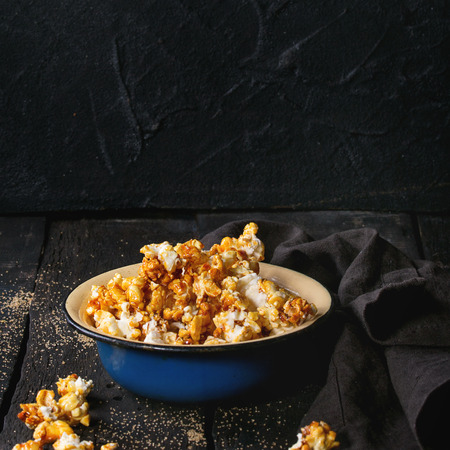enameled: Caramelized sweet popcorn served in vintage enameled bowl with brown sugar and textile napkin over dark wooden background. Square image. Stock Photo