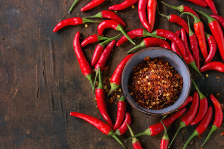 Heap of fresh red hot chili peppers with ceramic bowl of dry chilli flakes over old wooden textured background. Spicy theme. Top view Stockfoto