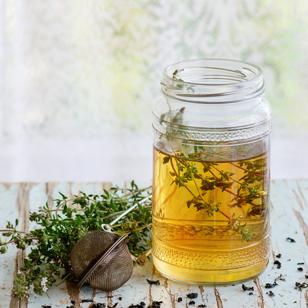 water thyme: Glass jar of hot herbal tea with bunch of fresh thyme, served with vintage tea-strainer on old wooden stool with window at background. Rustic style, natural day light. Square image.