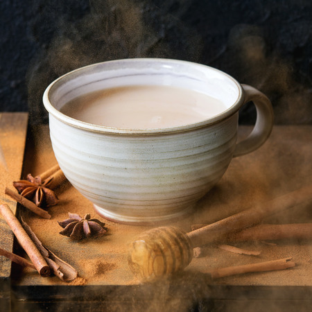 masala chai: White ceramic cup of hot masala chai, served with honey on honey dipper, anise, cinnamon sticks and powder over black wooden box over black background.