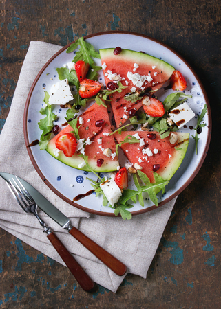 blue spotted: Blue spotted plate with watermelon and strawberry fruit salad with feta cheese, arugula, nuts and balsamic sauce, served with fork, knife and napkin over old dark wood background. Top view.