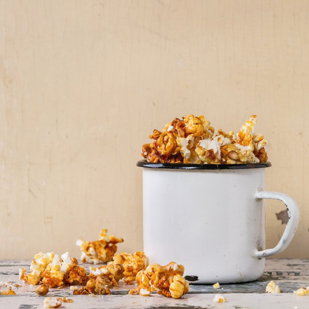 enameled: Prepared caramelized sweet popcorn served in vintage white enameled mug over old white wooden background. With space for text. Square image