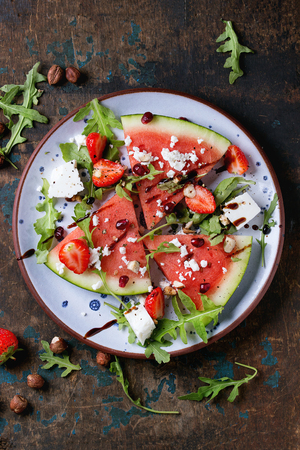blue spotted: Blue spotted plate with watermelon and strawberry fruit salad with feta cheese, arugula, nuts and balsamic sauce, served over old dark wood background. Top view.