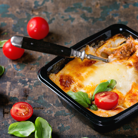 Cooked meat lasagna in black plastic box, served with vintage fork,  fresh cherry tomatoes and basil leaves over old dark wooden textured background. Square image