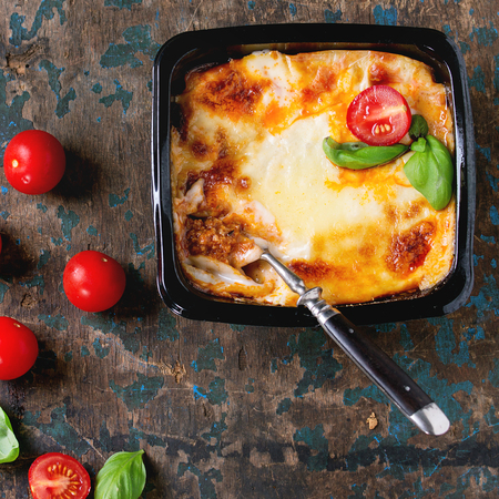 prepack: Cooked meat lasagna in black plastic box, served with vintage fork,  fresh cherry tomatoes and basil leaves over old dark wooden background. Top view. Square image