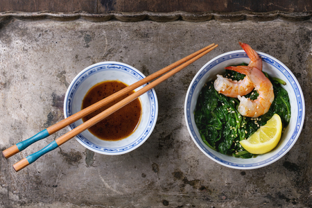 chinese spinach: Chinese bowls with Cooked spinach and fried shrimps prawns with lemon and sesame seeds, soy sauce and chopsticks over old iron background. Asian style dinner. Top view Stock Photo