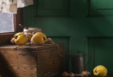 quinces: Three juicy quinces, walnuts and jar of honey over wooden table near window with bright sunlight. With green wooden wall at background. Dark rustic style.