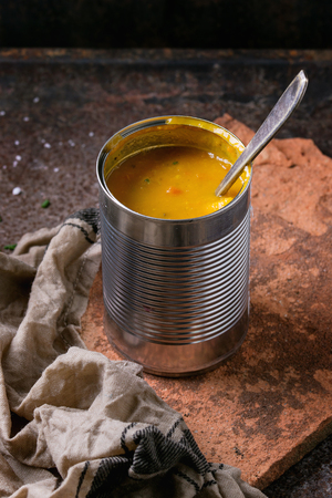 prepack: Tin can of carrot soup with spoon, standing on kitchen towel  and clay board over old rusty iron background. Dark rustic style Stock Photo