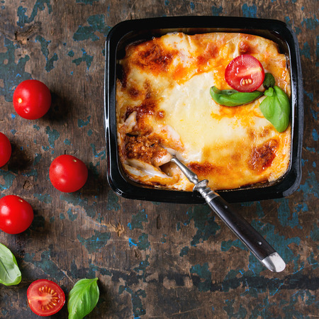 prepack: Cooked meat lasagna in black plastic box, served with vintage fork,  fresh cherry tomatoes and basil leaves over old dark wooden textured background. Top view, Square image